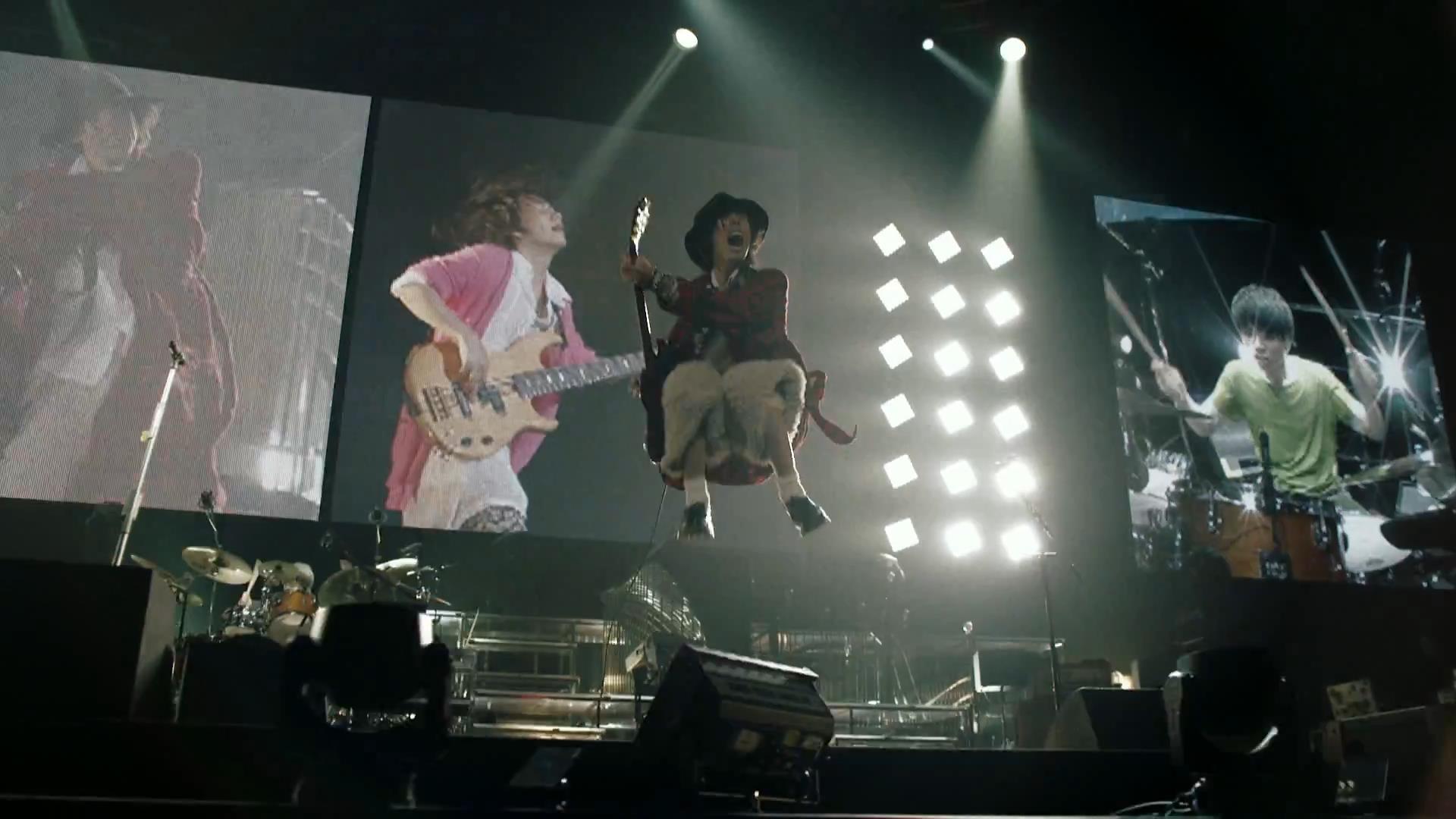 チェック柄の衣装で飛び跳ねるRADWIMPSの野田洋次郎